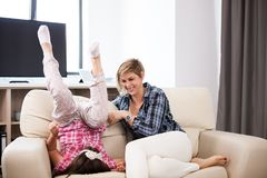 Middle aged woman on the couch with her teenage daughter. Middle aged women on the couch with her teenage daughter in the living room Stock Photo
