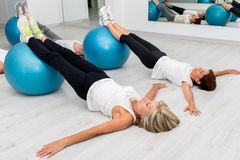Middle aged women doing leg exercises with fitness balls. Group of Middle aged women in health center doing leg exercises with fitness balls on floor stock photos