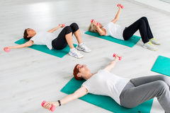 Middle aged women doing workout with weights. Group of middle aged women doing workout with weights. Women laying on rubber mattress on floor with dumbbells royalty free stock image