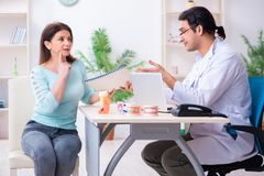 Middle-aged woman visiting male doctor stomatologist. The middle-aged women visiting male doctor stomatologist stock image