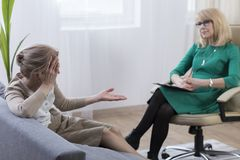 Middle aged woman visiting psychiatrist. Middle aged women visiting psychiatrist and talking about her problems, anxiety and stress Stock Image