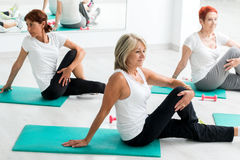 Middle aged women warming up in gym. Group of middle aged women warming up in gym.Threesome sitting on floor on rubber mattresses stock images
