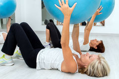 Middle aged women working out in gym. Group of Middle aged women exercising with fitness balls in health center stock photography