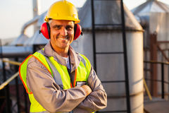 Middle aged worker. Happy middle aged oil chemical industry worker inside plant royalty free stock image