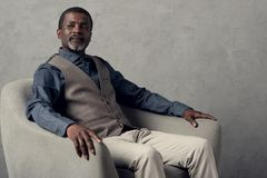 Middle agedf serious african american man. In waistcoat sitting in armchair stock images