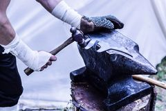 Medieval blacksmith with protective glove on hands manually forging metal for ax weapon with hammer on old anvil royalty free stock images