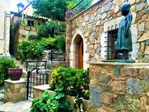 Medieval house and enchanting little garden in Tossa de Mar, Spain. Middle Ages, medieval house and wonderful little garden, statue, girl, fairytale, beauty stock photos