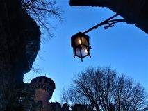 Middle Ages, medieval lamp and castle in Turin city, Italy. An ancient contruction and an enchanting atmosphere in a fairytale frame, among nature, under the royalty free stock image