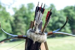 Medieval set of old wooden arrows in leather case and bows hanging on stand royalty free stock photography