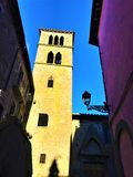 Middle Ages tower, pink building and shadows in Vitorchiano town, Italy. Middle Ages tower, pink building, street lamp, balcony, shadows, light, blue sky and stock photo