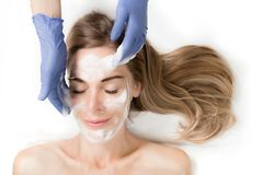 Middle aging beautiful woman cleaning her face with a foam treat. Applying facial foam clean fresh middle aging skin.  Woman in spa salon Royalty Free Stock Photos