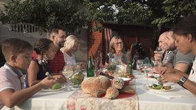 Big family reunion dinner. Middle angle of cheerful big American family sitting and eating in the garden during reunion party stock footage