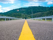 Middle of asphalt road on the dam background with mountain and w Stock Image