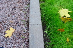 The middle of autumn. Park path, lawn and curbstone. Autumn abstraction with the fallen down maple leaves Stock Image