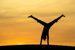 Middle of a cartwheel at sunset. Royalty Free Stock Image