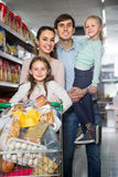 Middle-class family of  parents and two little children in hyper. Middle-class family of  parents and two little children doing shopping in hypermarket Stock Photos