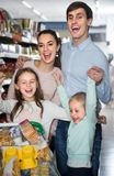 Middle-class family of smiling parents and two children in hyper. Middle-class family of smiling parents and two children doing shopping in hypermarket Royalty Free Stock Photos