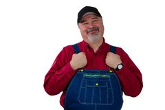 Middle-class farmer, worker, laborer or gardener. Standing holding the straps on his dungarees looking at the camera with a proud pleased smile isolated on Royalty Free Stock Photo