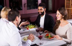 Middle class people enjoying food in cafe and talking. Positive middle class american people enjoying food in cafe and talking royalty free stock photo