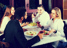 Middle class people enjoying food in cafe and talking. Smiling middle class european people enjoying food in cafe and talking royalty free stock image