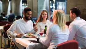Middle class people enjoying food in cafe terrace Stock Image