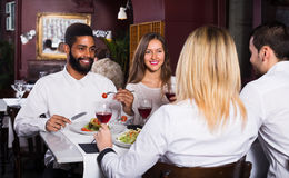 Middle class people enjoying food. Happy middle class people enjoying food in cafe and talking royalty free stock photo