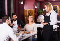 Middle class people enjoying food. Happy middle class people enjoying food in cafe and talking together stock image