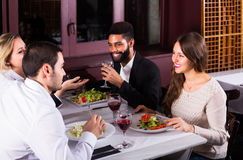 Middle class people enjoying food. Young middle class people enjoying food in cafe and talking stock photo