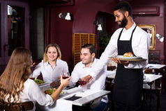 Middle class restaurant and cheerful waiter Royalty Free Stock Image