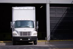 Middle class semi truck with box trailer for moving services sta. Middle class compact city rig semi truck with box trailer for moving services standing in Royalty Free Stock Photos