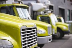Middle class semi trucks with box trailers for moving and delive. Middle class yellow semi trucks different makes and models with refrigerator unit on box Stock Image