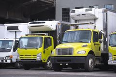 Small size local semi trucks with box refrigerator trailer stand. Middle class yellow and white semi trucks different makes and models with refrigerator unit on Stock Photography