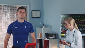 Middle close-up of athlete walking on treadmill and female doctor coming to monitor the process. In the background there is a big display with EKG data. In stock video footage