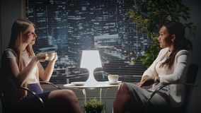 Middle close up of mixed race business women discussing something at the table with a cup of drink. There are skyscrapers in the background stock video footage