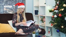 Middle close up of smart woman in Santa hat attentively reading book sitting on sofa at home. In the background there are skyscrapers. On the right there is a stock video