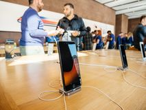Middle east ethnicity friends discussing New iPhone 8 and iPhone. PARIS, FRANCE - SEP 22, 2017: New iPhone 8 and iPhone 8 Plus charging in docking station goes Royalty Free Stock Photos