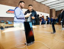 Middle east ethnicity friends discussing New iPhone 8 and iPhone. PARIS, FRANCE - SEP 22, 2017: New iPhone 8 and iPhone 8 Plus charging in docking station goes Stock Photography