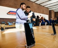 Middle east ethnicity friends discussing New iPhone 8 and iPhone. PARIS, FRANCE - SEP 22, 2017: New iPhone 8 and iPhone 8 Plus charging in docking station goes Stock Photo