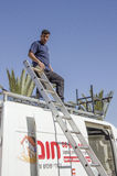 Middle East- Mitzpe Ramon, Israel -A worker with a ladder on the roof of the car Stock Images