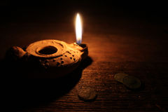 Middle East Oil Lamp and Old Coins. A burning clay oil lamp with old coins on a wooden table Stock Photos