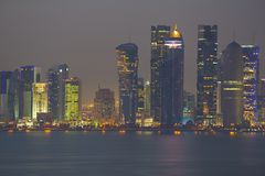 Middle East, Qatar, Doha, West Bay Central Financial District from East Bay District at Dusk Royalty Free Stock Photos