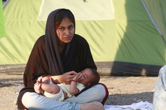 Middle East Refugees. A woman, immigrant from Middle East, feeds a young baby in the park near the bus station in Belgrade, Serbia, August 29, 2015. A large Royalty Free Stock Image