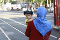 Middle East Refugees. A woman, refugee from Middle East, holds a young baby while going to take the bus for the border city with Hungary, in Belgrade, Serbia stock photography