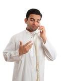 Middle eastern arab businessman on the phone. A middle eastern arab business man wearing an embroidered white kurta, thobe, robe, tunic, etc with ruby gemstone Royalty Free Stock Images