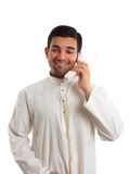 Middle eastern arab man using the telephone. A middle eastern man in traditional clothing is talking on a telephone Stock Images
