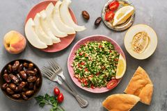 Middle Eastern or Arabic dish tabbouleh salad with pita bread on a gray background. Oriental sweets and fruits,melon, peaches , da