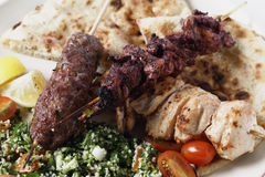 Middle Eastern barbecue meal. Various barbecued kebabs - kofta, chicken tawook and sumac chicken - with tabouleh and pitta bread; an Arab or Lebanese-style feast Stock Photography