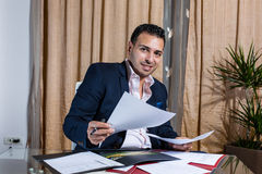 Middle Eastern businessman in the office. Middle Eastern businessman standing at his desk holding the business papers royalty free stock photo