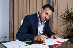 Middle Eastern businessman in the office. Middle Eastern businessman standing at his desk while signing the papers royalty free stock photography