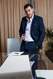 Middle Eastern businessman in the office. Middle Eastern businessman standing at his desk while signing the papers royalty free stock photos
